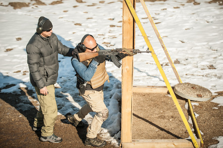 Instructor and his student had rifle machine gun shooting training on outdoor shooting range. Winter and snow cold season