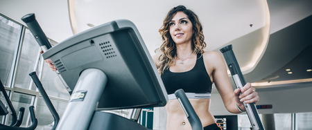 Attractive muscular smiling fitness woman running on treadmill in modern gym. Power fitness, sport, training, lifestyle 写真素材