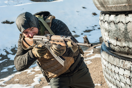 Special forces soldier in action, shooting from rifle machine gun. Outdoor winter and snow season Reklamní fotografie
