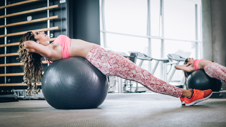 Attractive muscular smiling fitness woman doing exercise on pilates ball in modern gym. Power fitness, sport, training, lifestyle