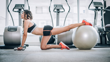 Attractive muscular smiling fitness woman doing exercise with dumbbells and pilates ball in modern gym. Power fitness, sport, training, lifestyle 写真素材