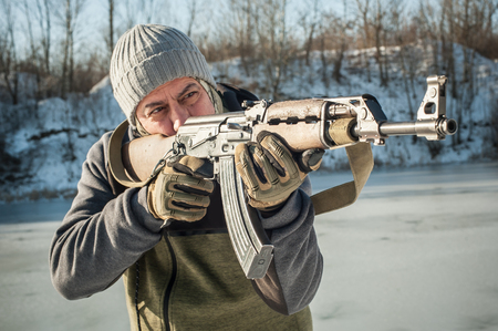 Instructor demonstrate body position of combat rifle shooting at winter deep snow. Advanced fighting tactical shooting courses on outdoor shooting range Reklamní fotografie