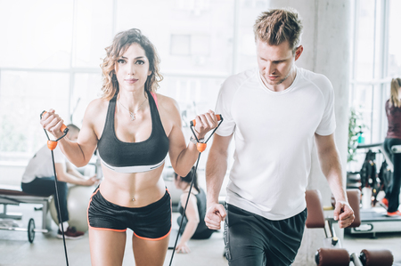 Attractive muscular smiling fitness woman with coach doing hard exercise in modern gym. Power fitness, sport, training, lifestyle