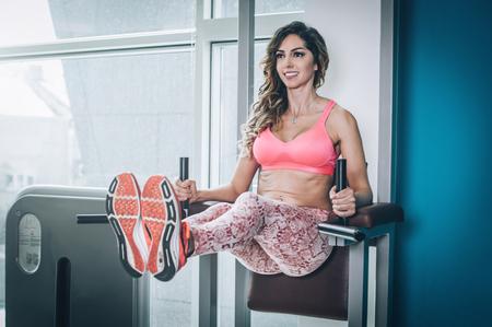 Attraktive muskulöse lächelnde Fitnessfrau, die harte Übung in der modernen Turnhalle tut. Kraftfitness, Sport, Training, Lifestyle