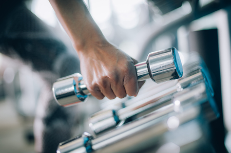 Close up of dumbbells in woman hand. Power fitness, sport, training, lifestyle
