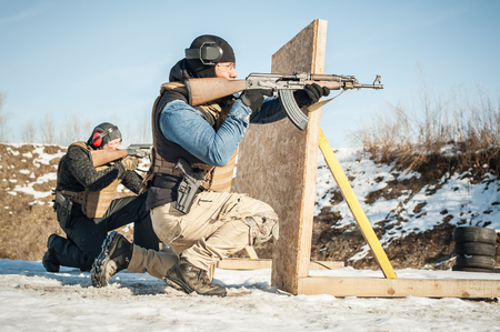 Special forces action shooting and moving defensive rifle firearm use training on outdoor shooting range. Winter and snow cold season Reklamní fotografie