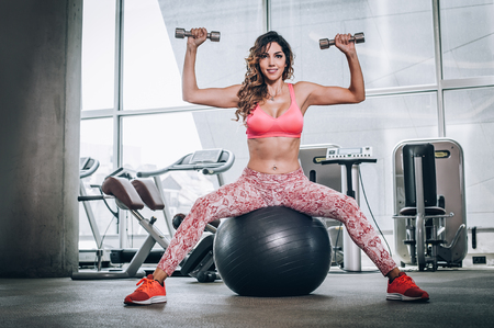 Attractive muscular smiling fitness woman doing exercise with dumbbells in modern gym. Power fitness, sport, training, lifestyle
