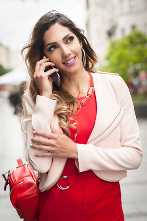 Outdoor portrait of a smiling happy young woman with smartphone, city street background