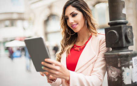 Young woman using digital tablet computer, surfing internet, city street background Stock Photo