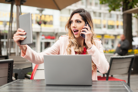 Hysterical young woman with too many screens, mobile phones, tablets and laptops. Too much communications concept. Internet social media. Emotional isolation and technology depresion Stok Fotoğraf
