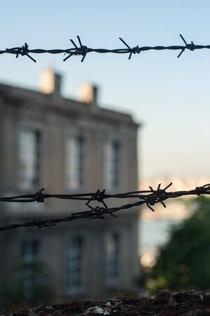 Barbed wire in front of the prison building. Close up