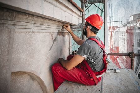 Mannelijke werknemer die oude bouwmuur pleistert met behulp van cementpleistermix van cement en zand op de bouwplaats Stockfoto