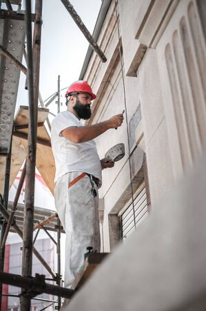 Construction mason worker plastering old building wall using cement plaster mix of cement and sand at the construction site