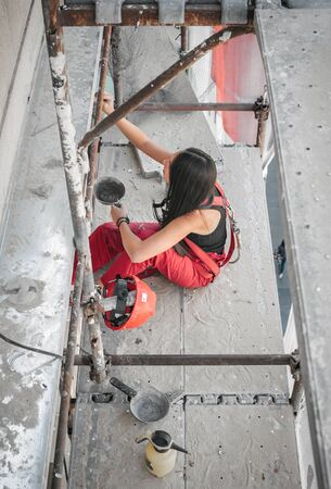 Female construction mason stands high on the scaffolding, plastering and renovating the wall on the old utility building Stock Photo