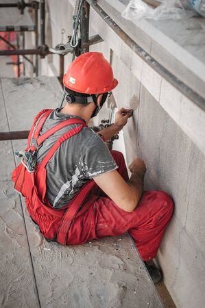 Male worker plastering old building wall using cement plaster mix of cement and sand at the construction site