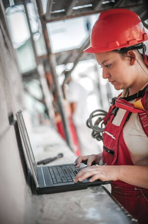 Female architect engineer stands high on the scaffolding inspects and checking progress at construction site on the laptop computer