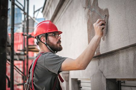 Man worker standing on scaffolding, perform work on the restoration of the facade of the old building. Repairing and renovate
