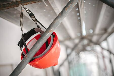 Safety helmet in construction site with scaffolding and working tools. Building renovation process