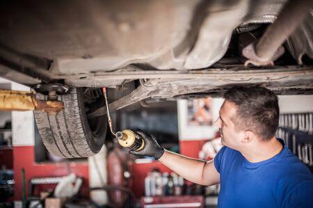Car master mechanic repairer heating the screws with butane gas blow mini welding torch flamethrower burner in vehicle repair service