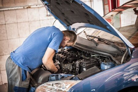 Car master auto mechanic repairer service technician checks and repairs the engine condition under the hood of the vehicle service shop