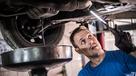 Auto mechanic repairer discharges old motor oil from the engine tank under the car on vehicle lift in workshop