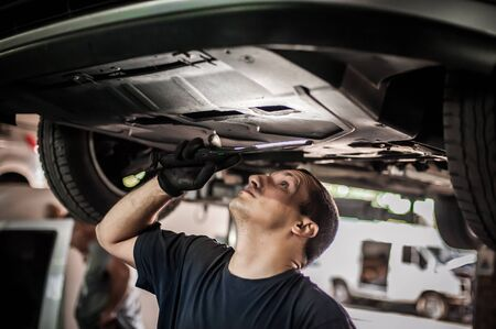 Master auto mechanic repairer service technician checking the condition under the car, on vehicle lift in workshop
