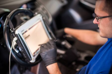 Automobile computer diagnosis. Car mechanic repairer looks for engine failure on diagnostics equipment in vehicle service workshop