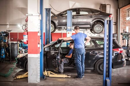 Automobile computer diagnosis. Car mechanic repairer looks for engine failure on diagnostics equipment in vehicle service workshop Stock Photo