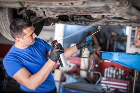 Car master mechanic repairer lubricates the screws with a machine parts cleaner oil dirt grease aerosol spray for lubrication