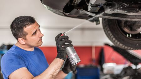 Car master mechanic repairer lubricates the screws with a machine parts cleaner oil dirt grease aerosol spray for lubrication in auto vehicle workshop Stock Photo