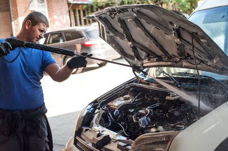 Car mechanic washes the car engine with pressurized water at service workshop