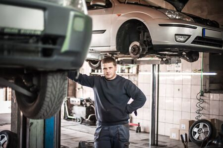 Car mechanic working in a repair garage with hydraulic car lift. Automobile elevator