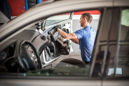 Car master mechanic works on the interior of a car door at vehicle service workshop Stock Photo
