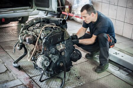 Removed engine from car. Car master auto mechanic repairer chacking and repair car engine in service workshop