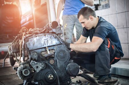 Removed engine from car. Two car master auto mechanic repairer chacking and repair car engine in service workshop Stock Photo