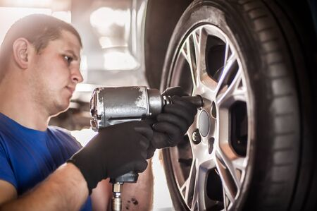 Car master mechanic vulcanizer replaces and changes old with new tires in auto vulcanizing and vehicle service workshop