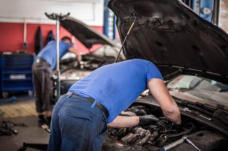 El técnico de servicio de reparadores mecánicos de automóviles maestros de dos automóviles comprueba y repara el estado del motor debajo del capó del taller de servicio del vehículo