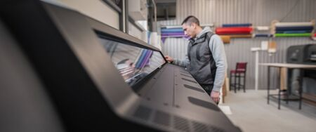 Technician operator worker checking input and output status on touchscreen front display monitor station in digital printshop office Imagens