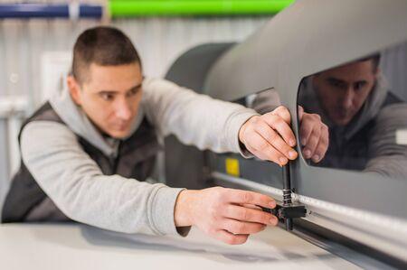 Electrical engineer operator repairs large premium industrial printer and plotter machine in digital printshop office