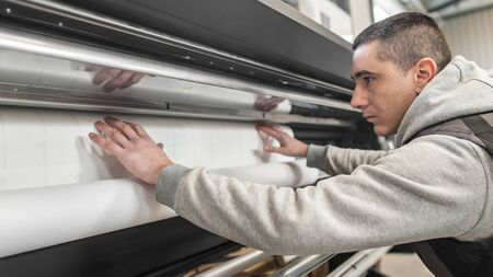 Technician worker operator changes the paper roll on large premium industrial printer and plotter machine in digital printshop office