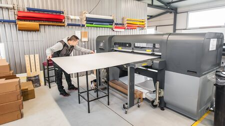 Technician worker operator works on large premium industrial printer and plotter machine in digital printshop office