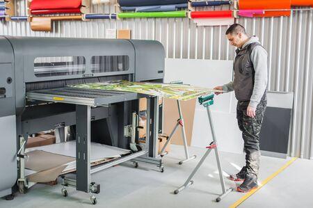 Technician worker operator works on large premium industrial printer and plotter machine in digital printshop office Imagens