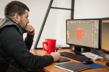 Graphic designer and 3d program animator work at computer in the office