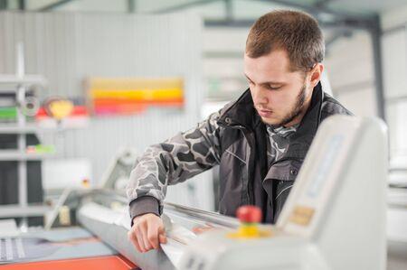 Worker printmaker technician glue large paper poster to foam board with semi automatic gluing machine in digital printshop office