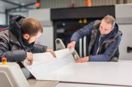 Two workers printmakers technicians glue large paper poster to foam board with semi automatic gluing machine in digital printshop office