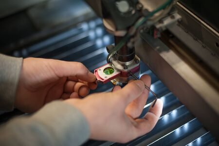 Electrical engineer repairs a laser cutting head on large CNC computer numerical control printing and cutting machine
