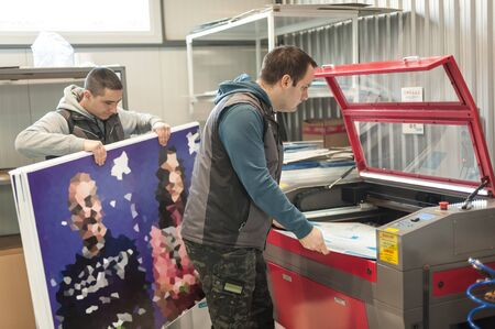 Two worker printmaker technician operator works in large digital printing press hall and printshop office with many different type of machine