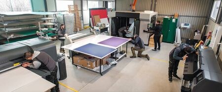 Large group of worker printmaker technician operator works in digital printing press hall and printshop office with many different type of machine