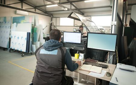 Technician operator engineer analyse status of printing jobs on the central computer in digital printshop office