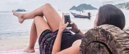 Close-up of casual girl using mobile phone and lie down on the beach sand with head on the wooden trunk. Technology and vacation concept Standard-Bild